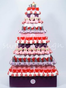 Tarta de pisos con chuches rojas, moradas y rosas