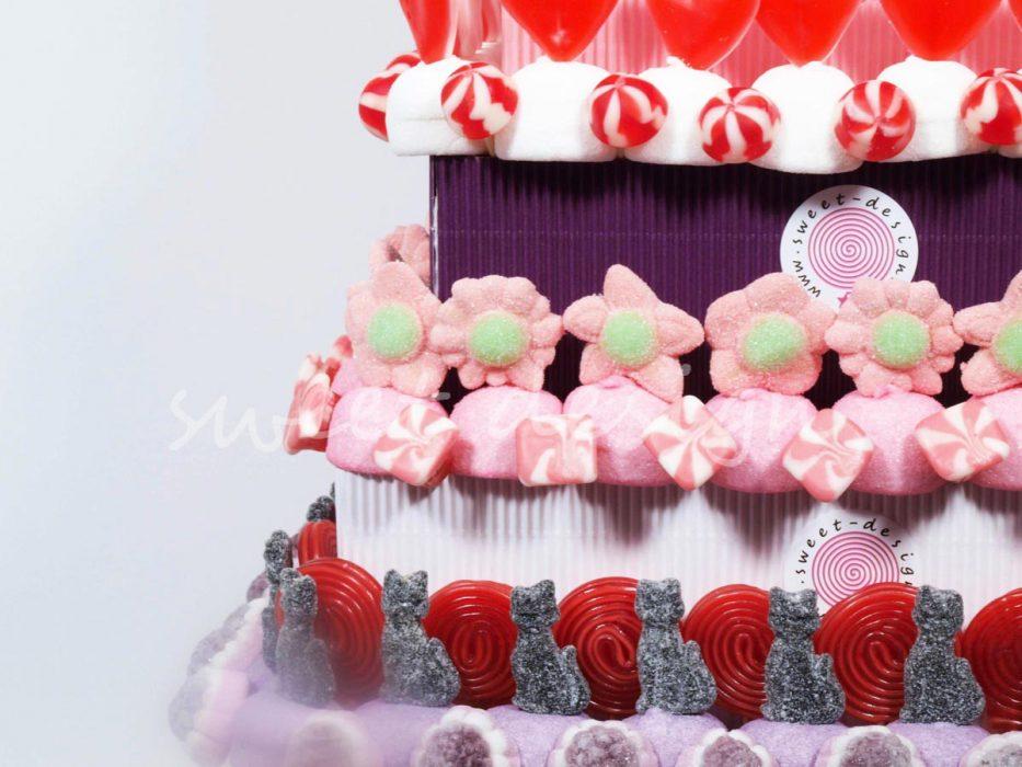 Pastel de 7 pisos con chuches rojas, moradas y rosas